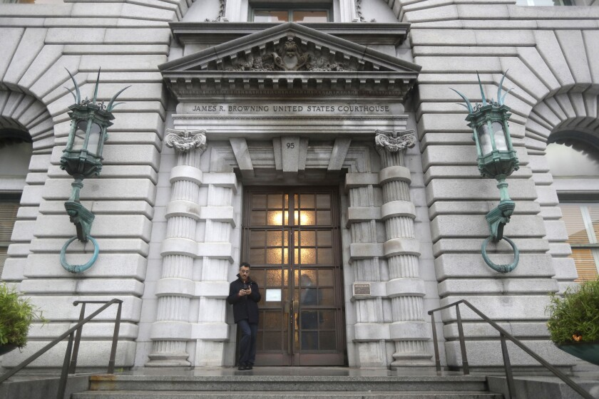 A man stands outside the main door of the U.S. 9th Circuit Court of Appeals building in San Francisco
