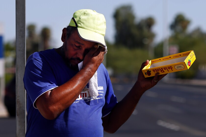 Asylum seeker Oswaldo Ortiz-Luna sells candy at a busy intersection in Mexicali, Mexico.