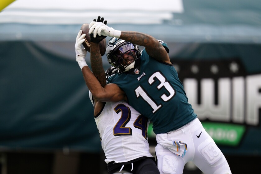 Philadelphia Eagles' Travis Fulgham (13) cannot catch a pass against Baltimore Ravens' Marcus Peters (24) during the second half of an NFL football game, Sunday, Oct. 18, 2020, in Philadelphia. (AP Photo/Chris Szagola)