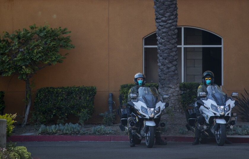 Orange County sheriff's deputies wear protective masks as they keep an eye on a Laguna Woods protest on April 4.