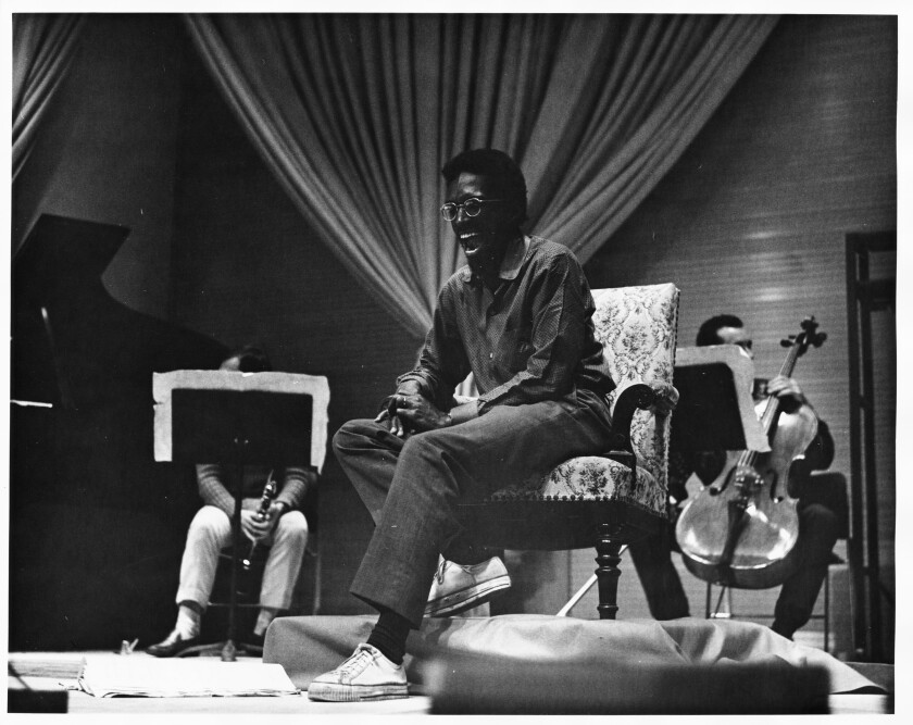 Julius Eastman seated in an armchair with instrumentalists around him.