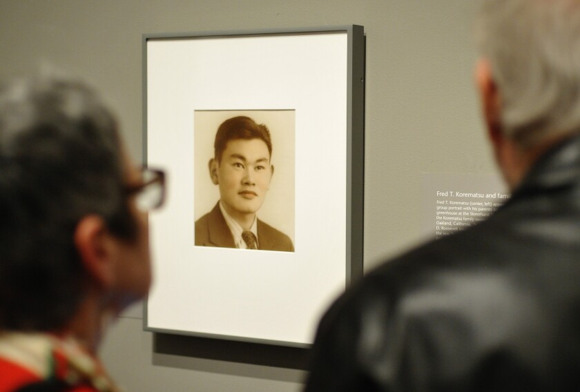 Guests look at a photograph of Fred Korematsu.
