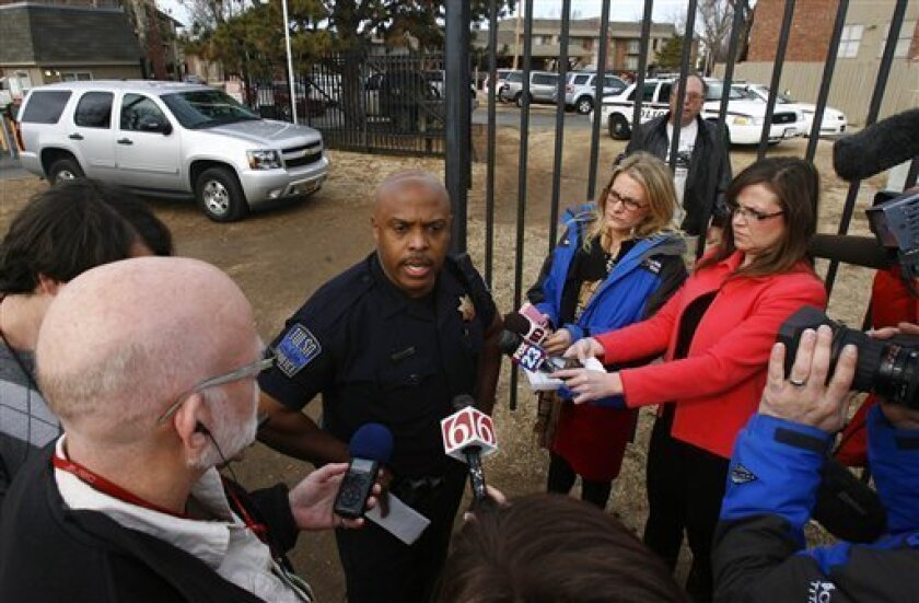 Officer Leland Ashley briefs reporters after a quadruple homicide at Tulsa's Fairmont Terrace apartment complex on Monday, Jan. 7, 2013. Four women were found shot to death inside an apartment, where a 4-year-old boy was also found unharmed. (AP Photo/Tulsa World, Matt Barnard ) TV OUT; TULSA OUT