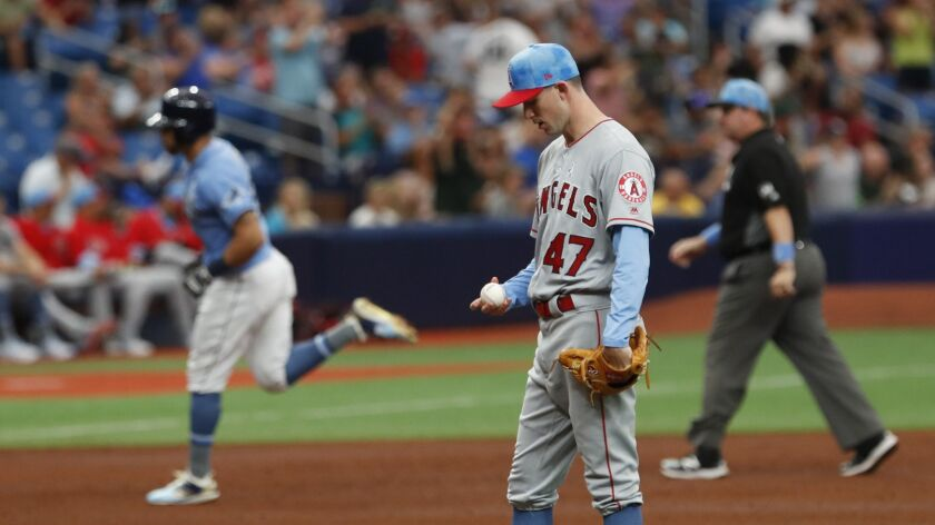 Los Angeles Angels pitcher Griffin Canning gives up a home run to Tampa Bay Rays Tommy Pham, behind