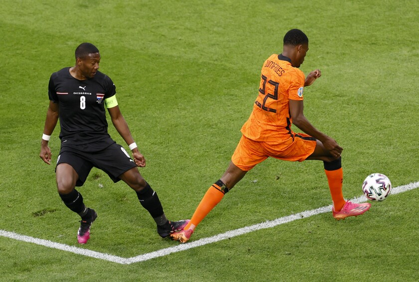 Austria's David Alaba, left, fouls Denzel Dumfries of the Netherlands to concede a penalty during the Euro 2020 soccer championship group C match between Netherland and Austria, at Johan Cruyff Arena in Amsterdam, Thursday, June 17, 2021. (Koen van Weel, Pool via AP)