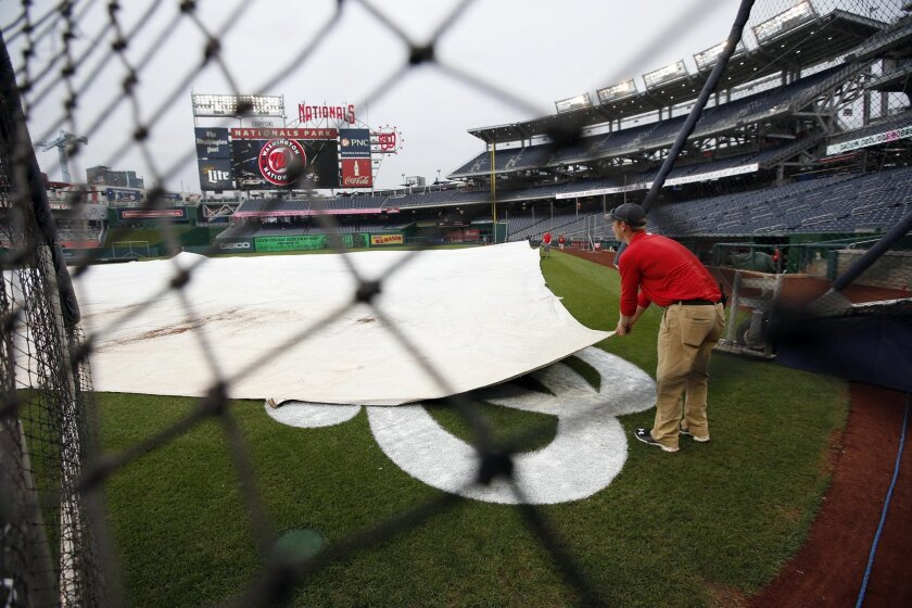 Members of the grounds crew adjust the tarp as the rain falls before a baseball game between the Washington Nationals and the Baltimore Orioles at Nationals Park, Monday, Sept. 21, 2015, in Washington. (AP Photo/Alex Brandon)