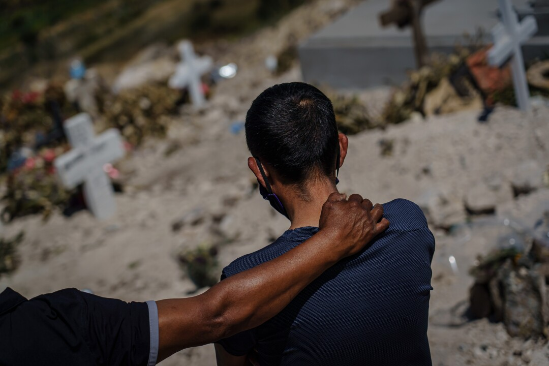 At Tijuana's Municipal Cemetery No. 13, Dominguez Hernandez consoles Fredy Villa Suerte Hernandez, right, as they mourn from a distance the death of Fredy's 49-year-old wife, Laura Moreno Sanchez, who died from COVID-19.