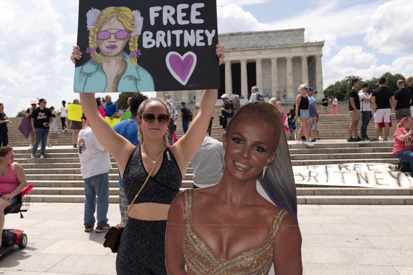 """FILE - In this July 14, 2021 file photo Maggie Howell supporter of pop star Britney Spears protests next to a Britney Spears cardboard cutout at the Lincoln Memorial, during the """"Free Britney"""" rally, in Washington. Spears' fight to end the conservatorship that controlled vast aspects of her life is putting the spotlight on ongoing efforts in U.S. states to reform laws that advocates say too often harm the very people they were meant to protect. (AP Photo/Jose Luis Magan,File)"""