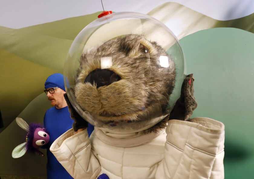 Gwen Hollander plays Astron-otter, the full-size otter dressed in a white astronaut suit. At left is Christian Anderson who plays Sy the Wide-Eyed Fly.