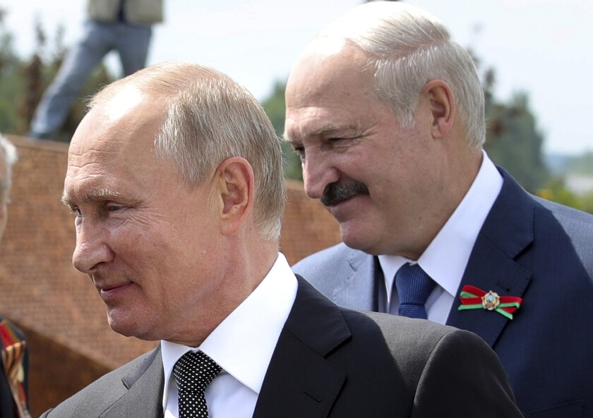 FILE - In this June 30, 2020, file photo, Russian President Vladimir Putin, left, and Belarusian President Alexander Lukashenko greet World War II veterans during the opening of a monument in their honor in the village of Khoroshevo northwest of Moscow, Russia. As Belarus experiences spasms of protests and a brutal police crackdown, its giant neighbor Russia has been uncharacteristically low key in response. (Mikhail Klimentyev, Sputnik, Kremlin Pool Photo via AP, File)