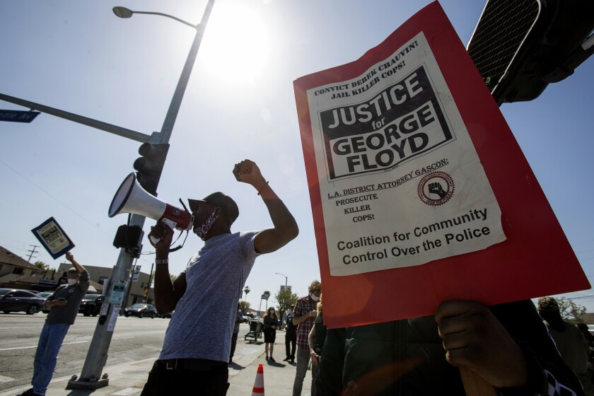 FILE — In this April 20, 2021, file photo, people take part in a rally in Los Angeles after a guilty verdict was announced at the trial of former Minneapolis police Officer Derek Chauvin for the 2020 death of George Floyd. Under a new law that went into effect July 1, the California Department of Justice will now be responsible for investigating the fatal police shootings of unarmed civilians, taking over from local agencies. The law was adopted last year amid civil unrest over the death of Floyd. (AP Photo/Ringo H.W. Chiu, File)