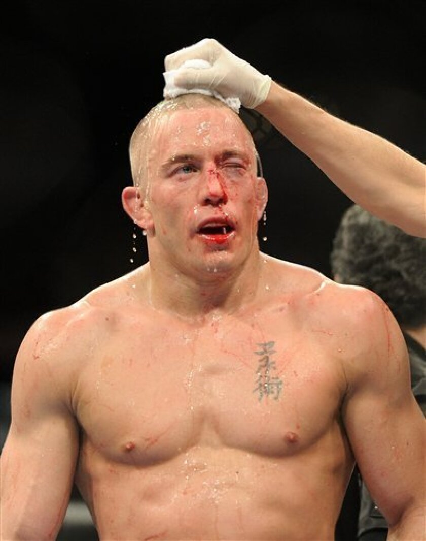 Fighter Georges St-Pierre gets watered down after defeating Jake Shields during the welterweight championship match at UFC 129 mixed martial arts match in Toronto on Saturday, April 30, 2011. (AP Photo/The Canadian Press, Nathan Denette)