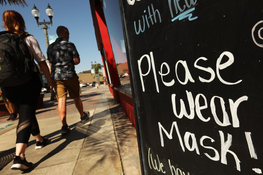 Pedestrians walk past a sign outside a business in Huntington Beach  urging customers to wear a mask on Aug. 12.