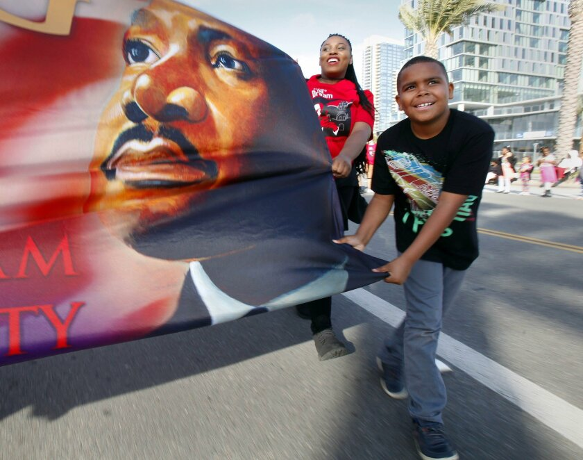 Terrell White, 9 (right), and Emmary Taylor hold a Martin Luther King Jr. banner during the parade.