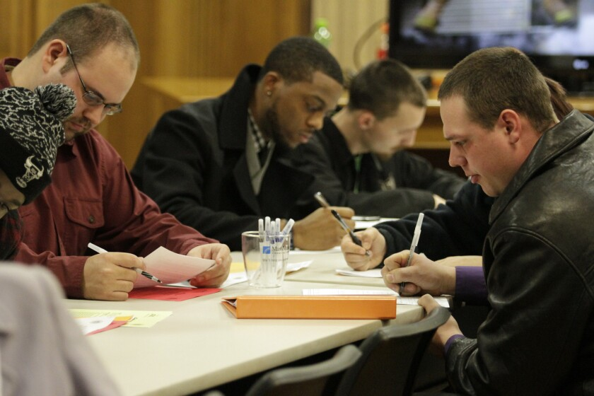 In this Jan. 29, 2015 photo, people fill out applications during a public safety job fair at City Hall in Saginaw, Mich.
