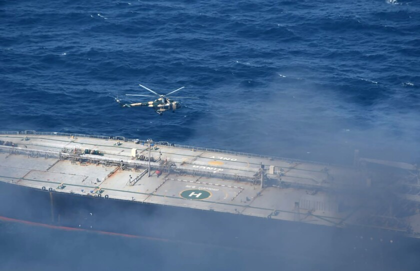 In this photo provided by Sri Lanka Air Force, a chopper flies through smoke rising from the MT New Diamond, off the eastern coast of Sri Lanka in the Indian Ocean,, Saturday, Sept. 5, 2020. The fire on the large oil tanker off Sri Lanka's coast has been brought under control but is still not extinguished, the navy said Saturday. The tanker, carrying nearly 2 million barrels of crude oil, was drifting about 20 nautical miles (37 kilometers) from Sri Lanka's eastern coast and on Friday evening a tug boat towed it to the deep sea away from land, said navy spokesman Capt. Indika de Silva. (Sri Lanka Air Force via AP)