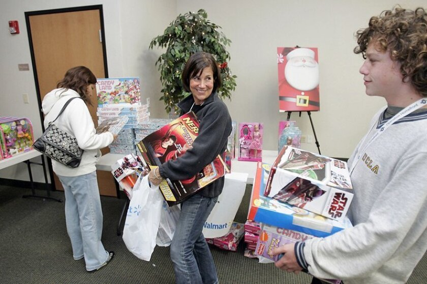 Marine Corps wife Denise Marie (left) picked up toys for her children with the help of volunteers Jennifer Axelrod (center) and her son Cole Axelrod, 16, both of Encinitas, during the Operation Homefront holiday giveaway in Oceanside yesterday.