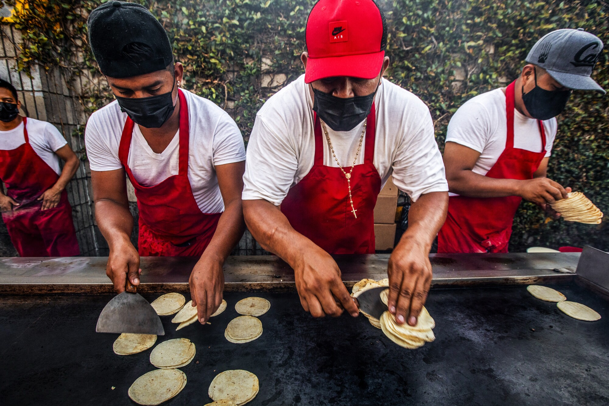 Cooks handle tortillas on and near a flat-top grill.