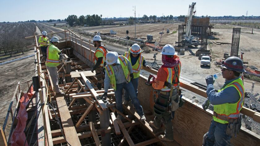 Crews construct a pier cap at the Road 27 overcrossing during bullet train construction in Madera Co