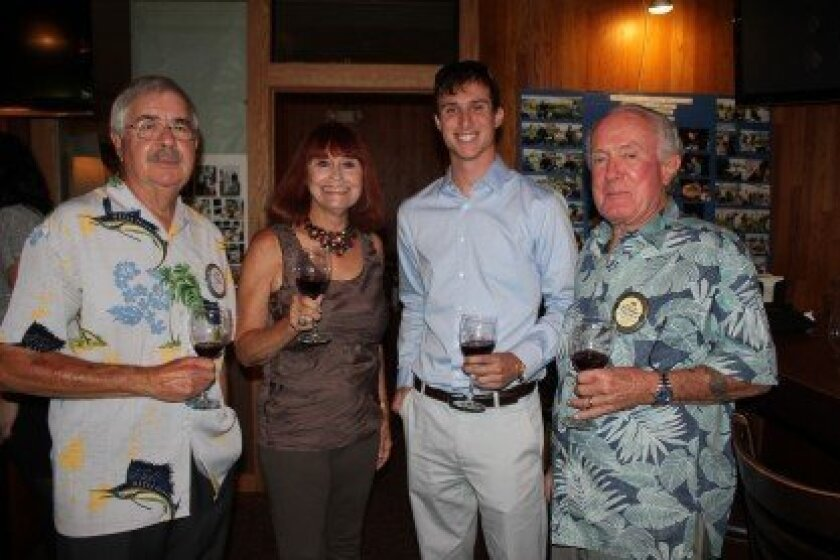 Rotary club member Mike Cummings, Carol Irwin, visitor Ricky Barrett and past Rotary president Jim Likes partake of the club's weekly wine social.