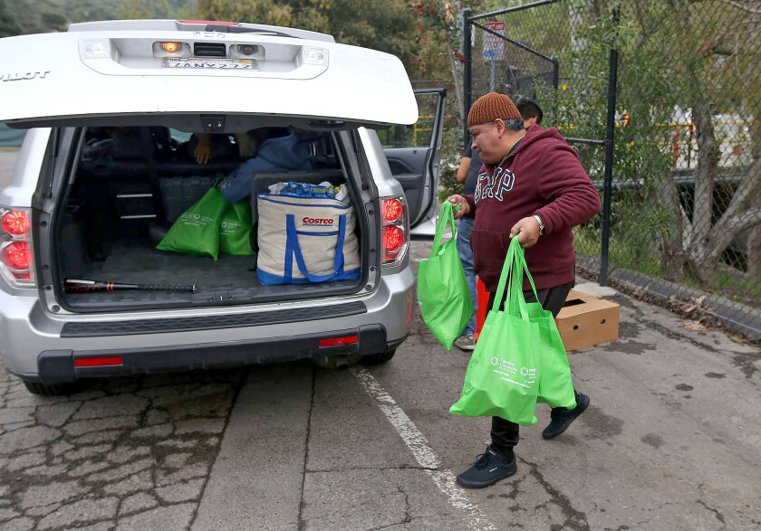 Customers pick up groceries during drive-up distribution outside the Laguna Food Pantry on Wednesday. Shoppers normally would go inside the pantry, but it is now serving people outside to follow precautions against the coronavirus.