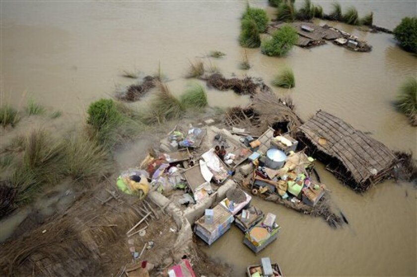 A Pakistani family stands at their house submerged in heavy floodwater in Mithan Kot, in central Pakistan, Monday, Aug. 9, 2010. The government has struggled to cope with the scale of the disaster, which has killed at least 1,500 people, prompting the international community to help by donating t