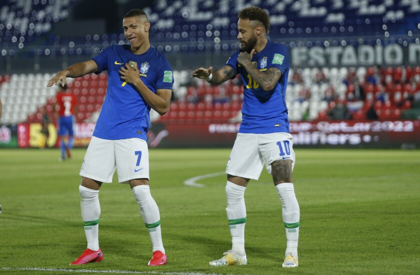 Brazil's Neymar, right, celebrates with teammate Richarlison after scoring his side's opening goal against Paraguay during a qualifying soccer match for the FIFA World Cup Qatar 2022 at Defensores del Chaco stadium in Asuncion, Paraguay, Tuesday, June 8, 2021. (AP Photo/Jorge Saenz)