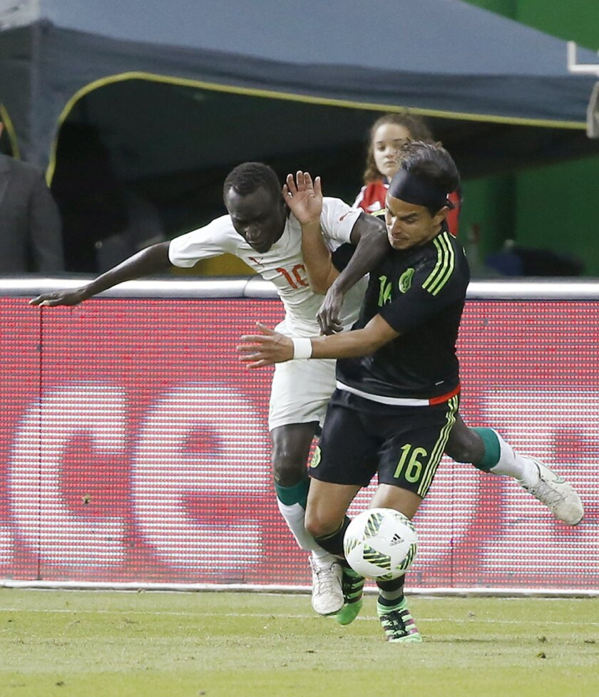 Senegal's Cherif Salif Sane (10) and Mexico's Jorge Torres Nilo (16) battle for the ball during the second half of a soccer match at Marlins Park, Wednesday, Feb. 10, 2016, in Miami. Mexico defeated Senegal 2-0. (AP Photo/Wilfredo Lee)
