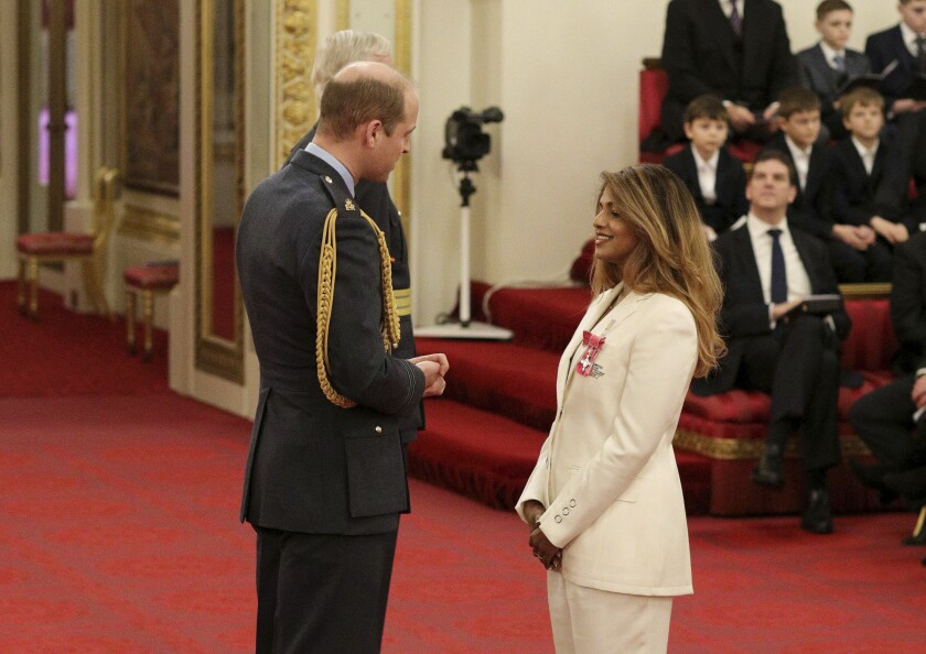 Rapper and singer MIA, real name Mathangi Arulpragasam, is made an MBE by Prince William Duke of Cambridge, left, at Buckingham Palace, in London, Tuesday Jan. 14, 2020. The honorary award is conferred in recognition of contributions to the arts, sport, sciences, and charitable works. (Jonathan Brady/PA via AP)