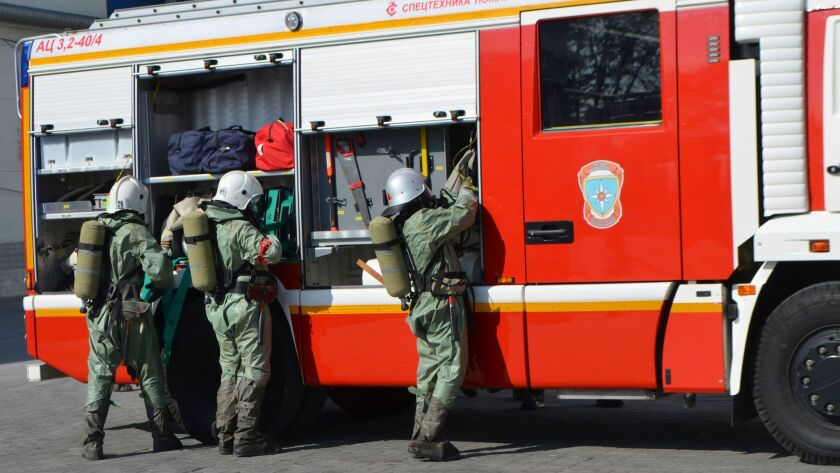 In this Oct. 5, 2016, photo provided by Russia Emergency Situations Ministry press service, the ministry servicemen wearing anti-chemical hazard suits unload firefighters' equipment at an undisclosed location in Russia.