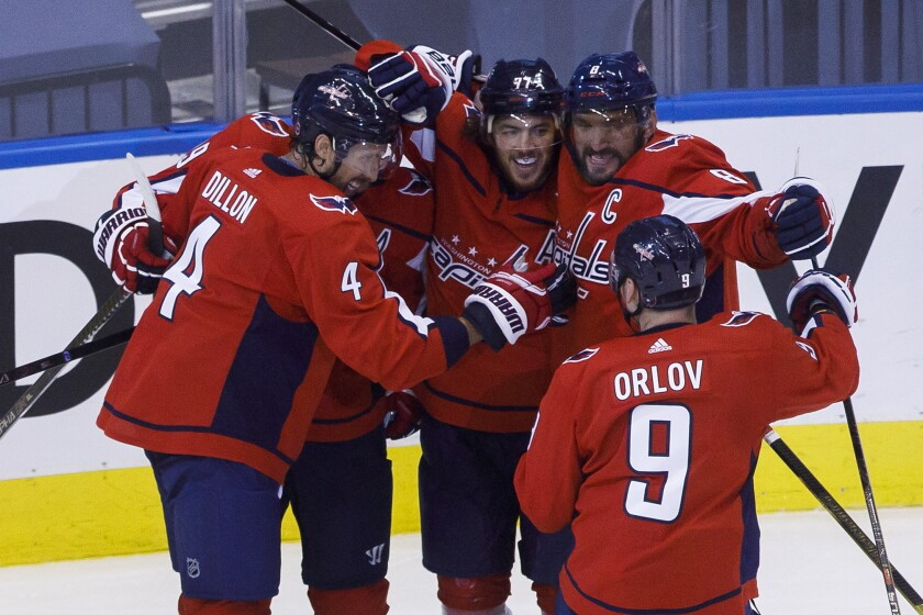 Washington Capitals left wing Alex Ovechkin (8), right wing T.J. Oshie (77), center Nicklas Backstrom (19), defenseman Brenden Dillon (4) and defenseman Dmitry Orlov (9) celebrate Oshie's goal against the Boston Bruins during first-period NHL hockey Stanley Cup qualifying round game action in Toronto, Sunday, Aug. 9, 2020. (Cole Burston/The Canadian Press via AP)
