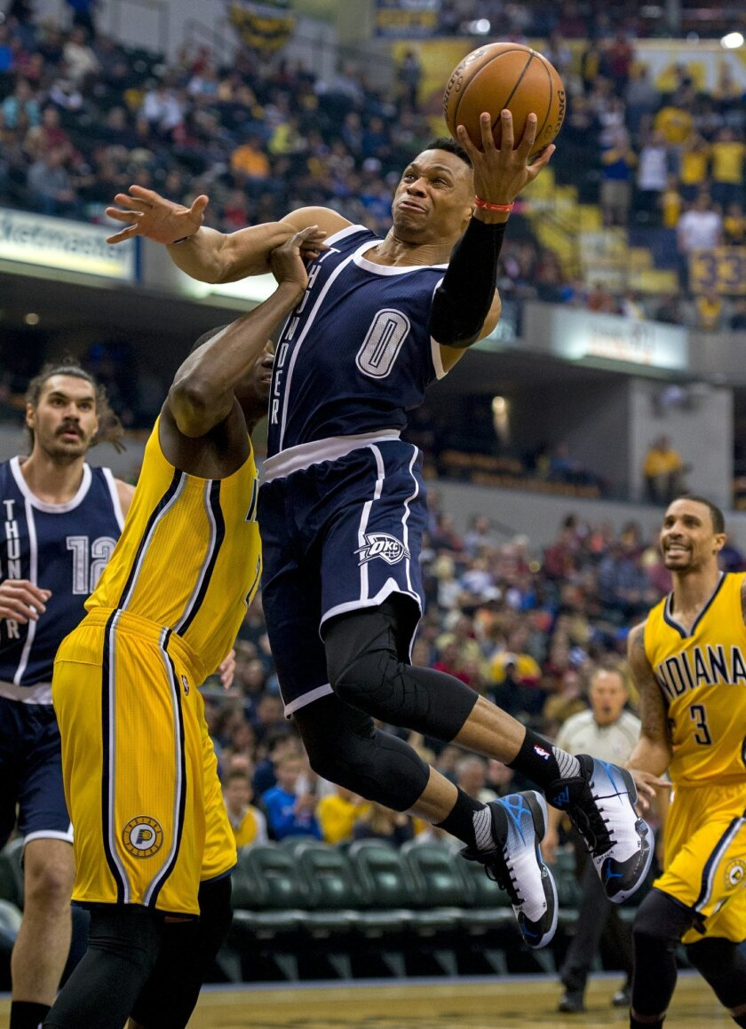 Oklahoma City Thunder guard Russell Westbrook (0) drives the ball to the basket and around the defense of Indiana Pacers center Ian Mahinmi (28) during the first half of an NBA basketball game Saturday, March 19, 2016, in Indianapolis. (AP Photo/Doug McSchooler)