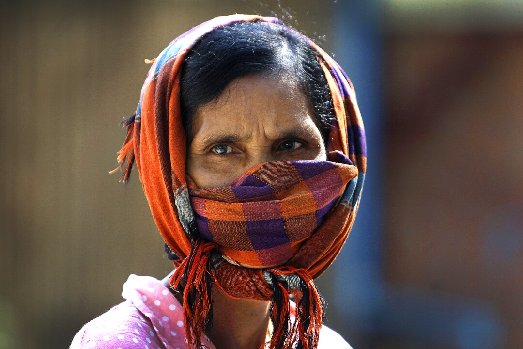 CAMBODIA: A woman dons a scarf as she watches social workers spray disinfectant to help curb the spread of the coronavirus in the slum neighborhood of Stung Meanchey in southern Phnom Penh.