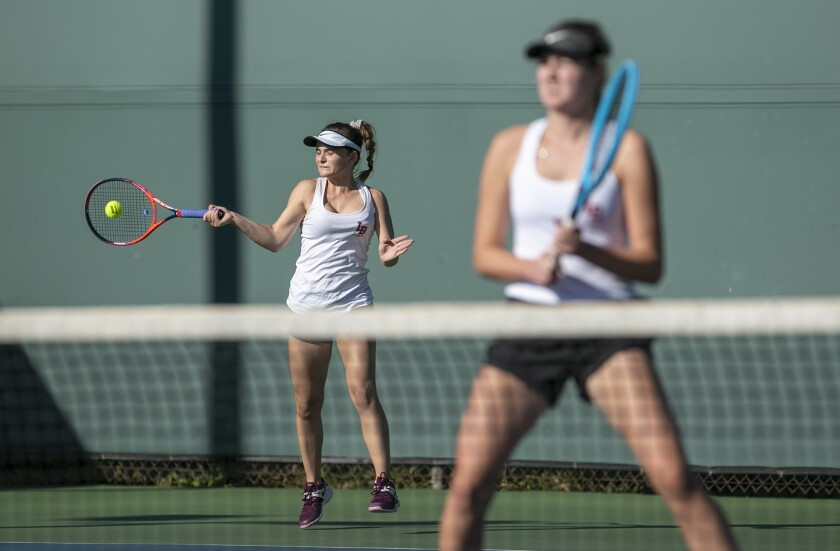 Laguna Beach's Sarah MacCallum, left, returns a shot as her partner, Ella Pachl, waits at the net in the CIF Southern Section Individuals doubles title match against Beckman's Kiki Nguyen and Victoria Aguirre on Monday at Seal Beach Tennis Center.