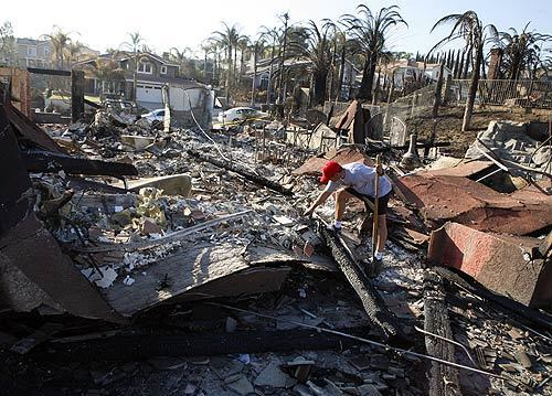 Jim McElroy sifts through the debris of his home on Aviemore Drive in Yorba Lnda four days after the fires swept through the hills.