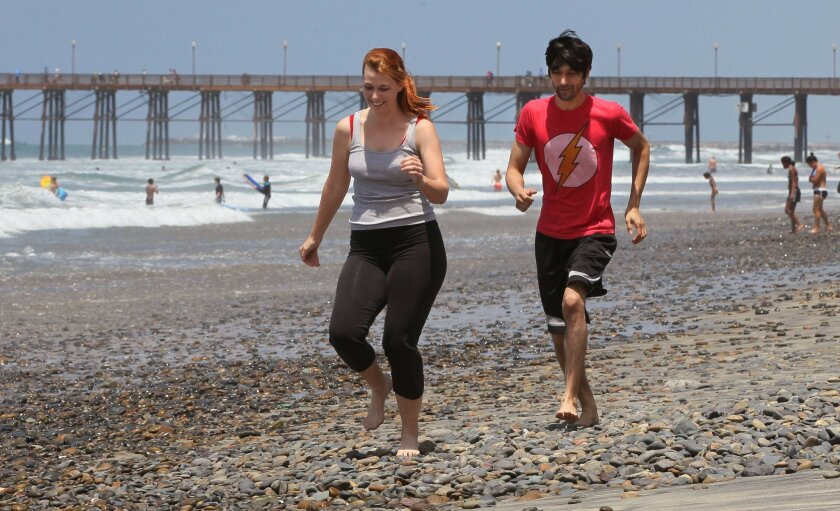 Joggers dodge rocks on the beach near Tyson Street Park, south of the Oceanside Pier after surfing.