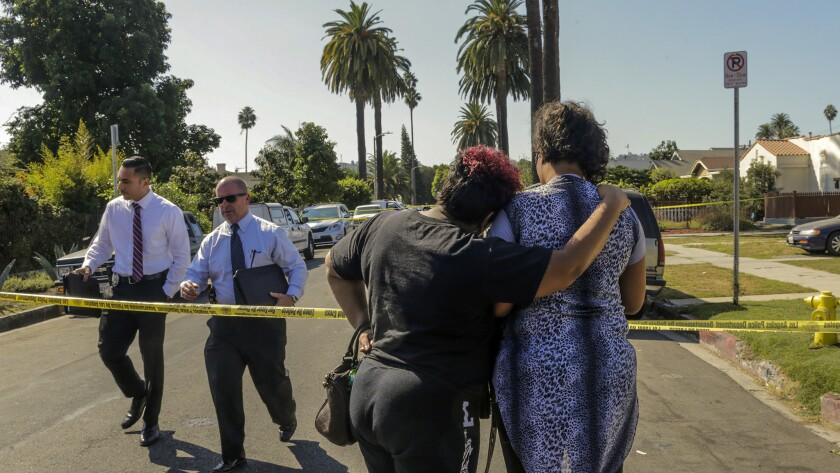 A woman comforts the wife of a man who died in a shooting that left four dead and 12 others wounded at a home on 2900 block of South Rimpau Boulevard in West Adams.