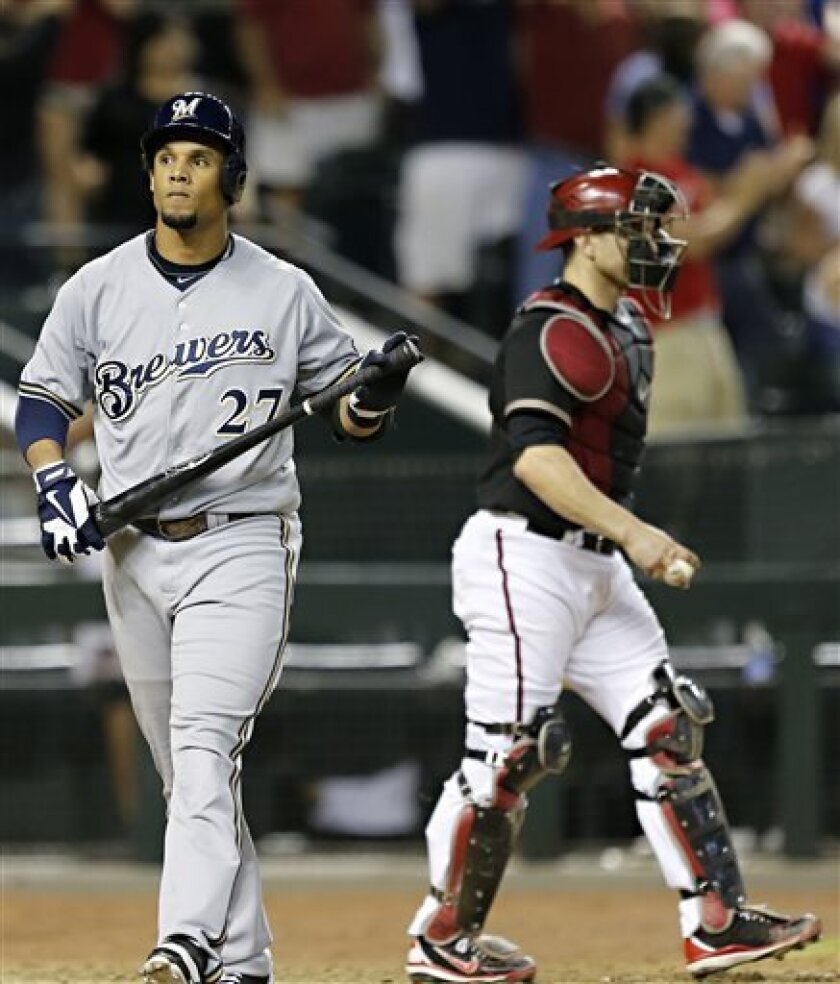 Arizona Diamondbacks' Miguel Montero, left, walks away as Milwaukee Brewers' Carlos Gomez strikes out to end the baseball game, Friday, July 12, 2013, in Phoenix. The Diamondbacks won 2-1. (AP Photo/Matt York)