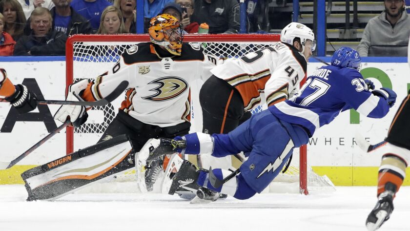 Ducks defenseman Andy Welinski (45) sends Tampa Bay Lightning center Yanni Gourde (37) flying after a check in front of goaltender Ryan Miller (30) during the first period on Tuesday.