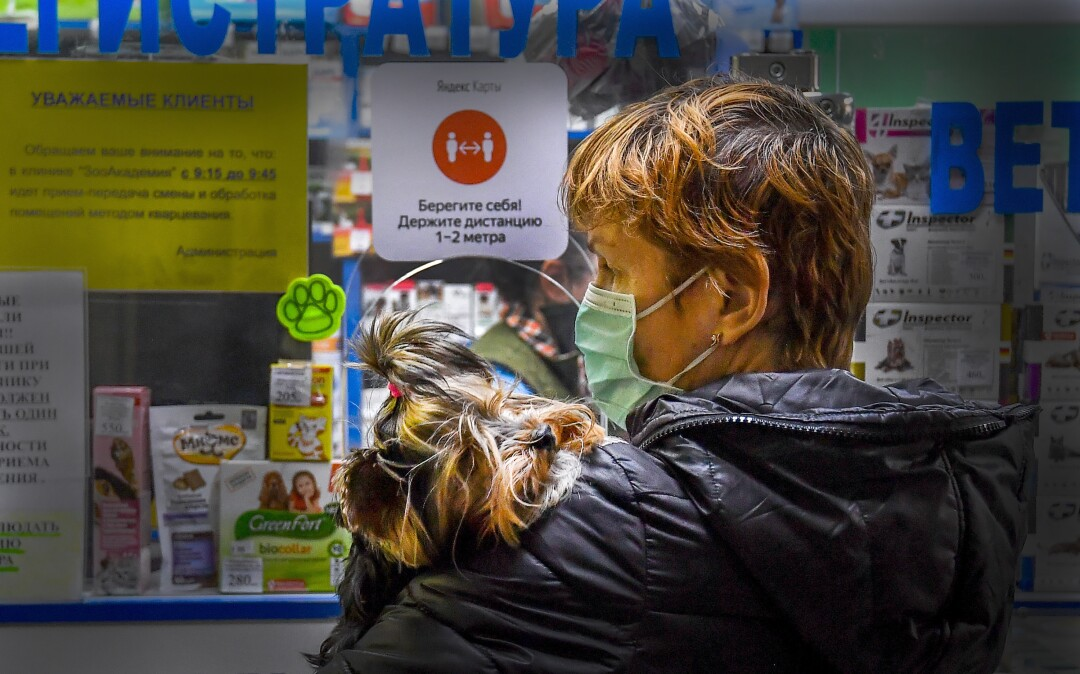 "RUSSIA: A woman wearing a face mask holds her dog as she visits ""ZooAcademy"" veterinary clinic in Moscow on April 21, 2020, during a strict lockdown in Russia to stop the spread of the COVID-19 coronavirus."