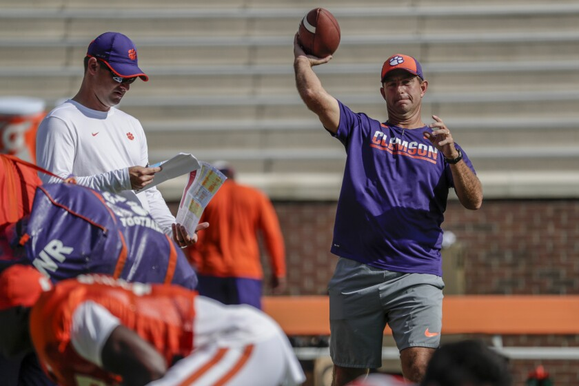 Clemson coach Dabo Swinney throws a football during a team practice session.