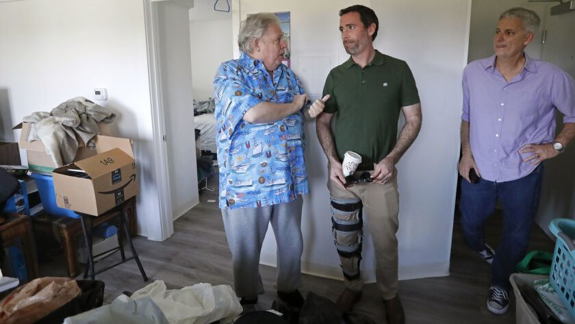 Navy veteran Glen Lipton, 67, left, talks to Kyle Paine, Community Development Partners president, c