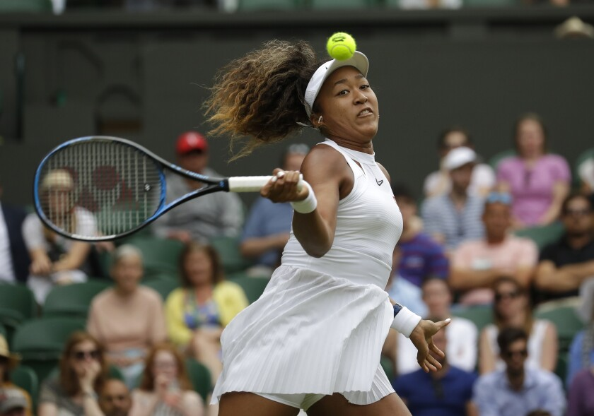 """FILE - Japan's Naomi Osaka returns to Kazakstan's Yulia Putintseva in a women's singles match during day one of the Wimbledon Tennis Championships in London, in this Monday, July 1, 2019, file photo. Osaka's agent says the four-time Grand Slam champion will sit out Wimbledon and compete at the Tokyo Olympics. Stuart Duguid wrote Thursday, June 17, 2021, in an email that Osaka """"is taking some personal time with friends and family. She will be ready for the Olympics and is excited to play in front of her home fans."""" (AP Photo/Kirsty Wigglesworth, File)"""