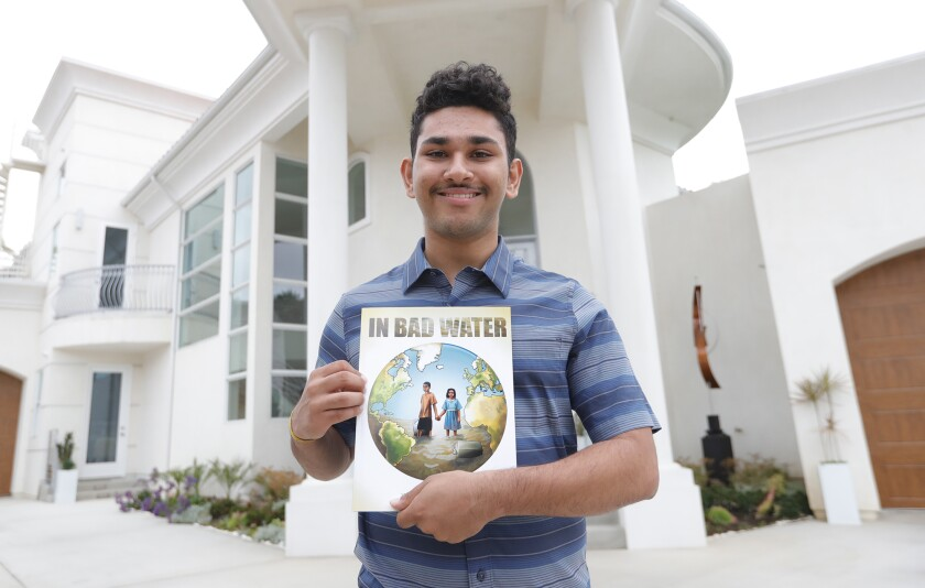 """Arjun Vij, 18, a senior at Corona del Mar High, holds a copy of his self-published book """"In Bad Water."""""""