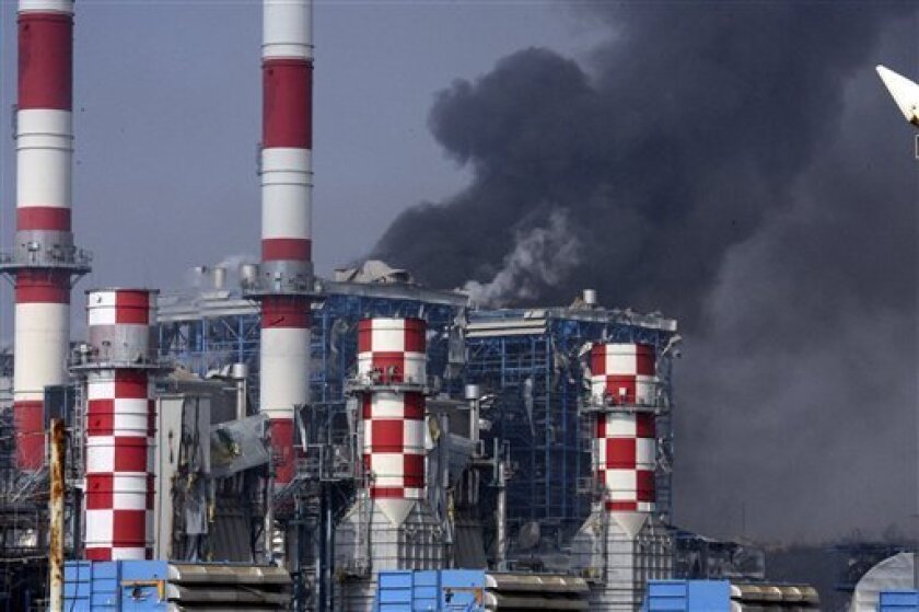 Smoke billows from the damaged Mari power station _ the island's primary electricity generator _ damaged by the explosion's concussion wave near the Evangelos Florakis naval base in Mari, Cyprus, Monday July 11, 2011. A huge explosion tore through a Cypriot National Guard naval base causing widespread damage, the Defense Ministry said. At least 10 people were feared dead. A bush fire ignited gunpowder stored in containers that Cypriot authorities confiscated in 2009 from a ship sailing off its coast. The ship, the Cypriot-flagged Monchegorsk, had been suspected of heading from Iran to Syria, with gunpowder destined for Gaza. It was seized in February 2009. (AP Photo/Philippos Christou)