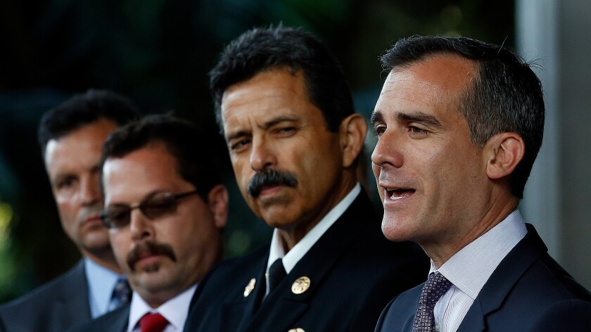 L.A. Mayor Eric Garcetti, right, stands next to city Fire Chief Ralph M. Terrazas. Terrazas said in a staff memo that Fire Marshal John Vidovich will step down next month.
