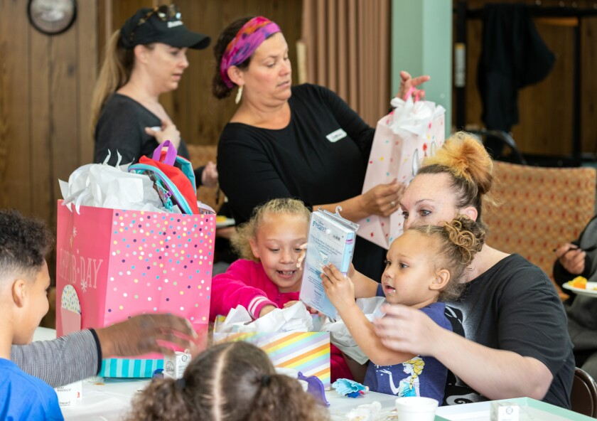 Oceanside Sanctuary congregation member Vanessa Graziano, top center, coordinates volunteers and donations to a homeless resources fair held at the church the second Saturday of each month. This past Saturday she handed out to birthday gifts to three-year-old Zora Sauls, second from right, along with her sister, Olivia Sauls and her mom, Chelsea Roberts.