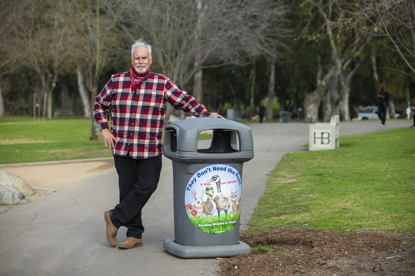 Steve Engel  with a decal urging people not to feed wildlife in Central Park in Huntington Beach.