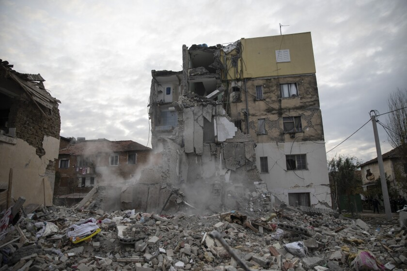 In this Wednesday, Nov. 27, 2019 photo, dust rises from the falling parts of a destroyed building during an aftershock in Thumane, western Albania. The 6.4-magnitude quake that hit Albania's Adriatic coast before dawn on Tuesday has left at least 51 people dead, around 2,000 others injured and about 4,000 people homeless. (AP Photo/Petros Giannakouris)