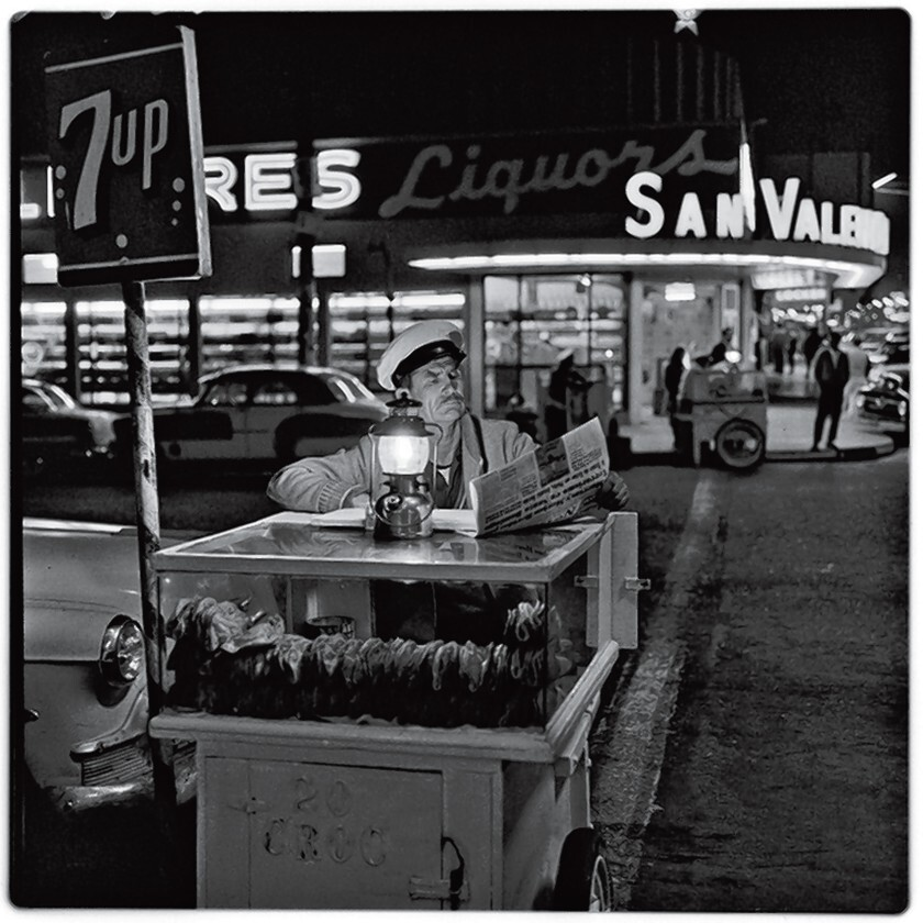 A taco vendor catches up on the news until the next customer shows up in this 1964 photograph by Harry Crosby, in the collection of Paul Ganster.